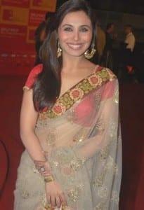 L'actrice Rani Mukherjee en sari transparent aux motifs dorés sur une blouse rouge.